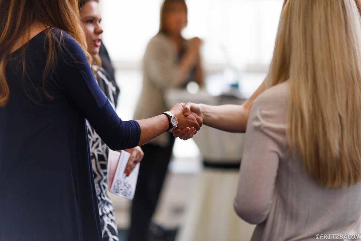 Close up of handshake, featuring women in the foreground and background