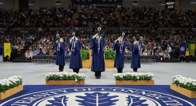 image of commencement ceremony, students in gowns playing brass instruments