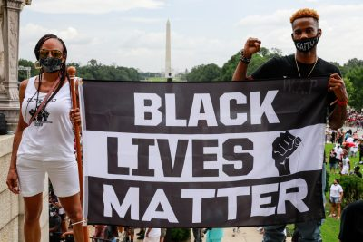 photo of two people holding a Black Lives Matter flag