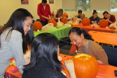 photo of COMM grad students carving pumpkins