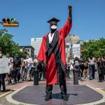 photo of Black man in academic regalia in the center of a Black Lives Matter assembly